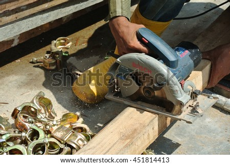 Carpenter using electrical powered circular saw to cut plywood at the construction site in Malacca, Malaysia.