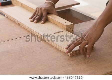 Carpenter using table saw cutting wood.