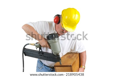 Carpenter wearing hearing protection and a hard hat, working a pneumatic nail gun constructing a box over a white background - stock photo