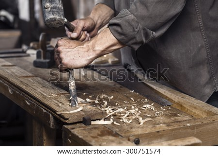 Carpenter with a hammer and chisel on the wooden workbench in carpentry - stock photo