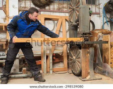 Carpenter with a plank on an electric saw machine
