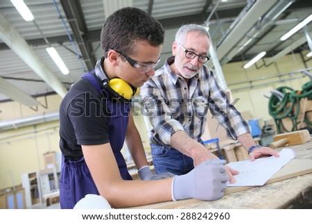 Carpenter with apprentice in training period - stock photo