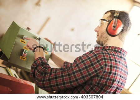 Carpenter with automatic circular saw. He has protective glasses. - stock photo