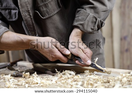 carpenter with chisel in the hands on the workbench in carpentry - stock photo