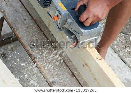 Carpenter with electric plane outdoors