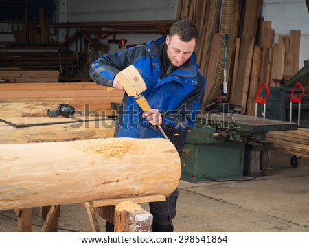 Carpenter with mallet and chisel in his workshop