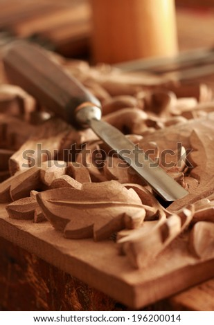Carpenter wood chisel tool with carving on old weathered wooden workbench - stock photo