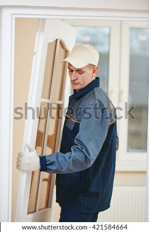 carpenter worker at door installation - stock photo