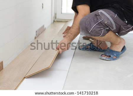 Carpenter worker installing laminate board during flooring work - stock photo