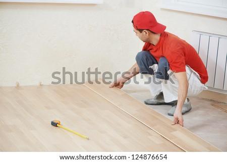 carpenter worker installing wood parquet board during flooring work - stock photo