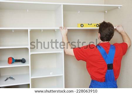 carpenter worker joint and settle home built-in cupboard - stock photo