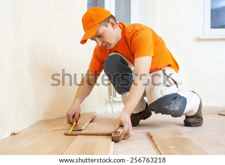 carpenter worker measuring wood parquet board during flooring work with hammer - stock photo