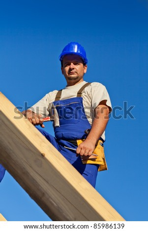 Carpenter worker on top of wooden structure looking down - stock photo