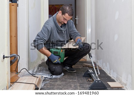 Carpenter working in a narrow passage sanding and cutting new floor boards to be installed during renovations after removing the old floor tiles - stock photo