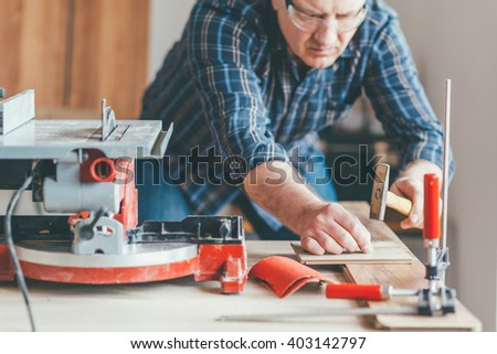 Carpenter working in his workshop . Small depth off field and selective focus.