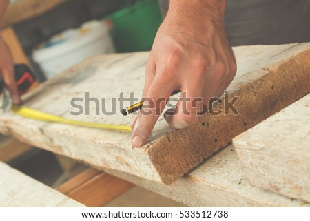 Carpenter working on raw wood.