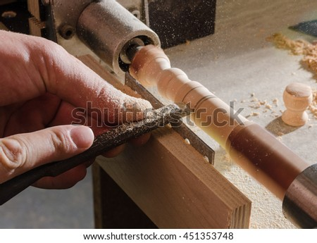 Carpenter working on the machine grind out piece of furniture