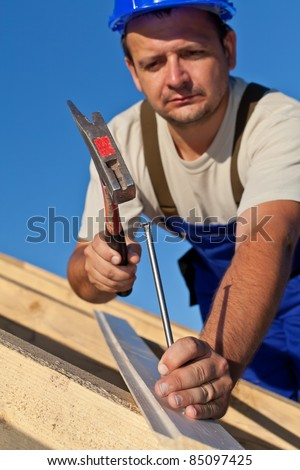 Carpenter working on the roof driving a nail in - shallow depth - stock photo