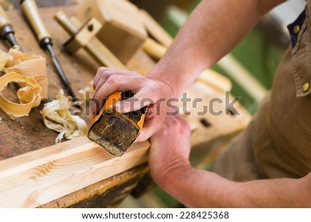 Carpenter working with a sanding block and sandpaper in his workshop
