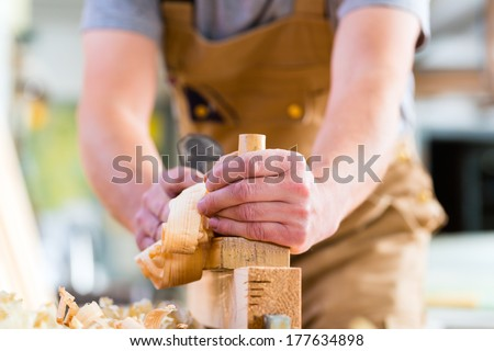 Carpenter working with a wood planer on workpiece in his workshop or carpentry - stock photo