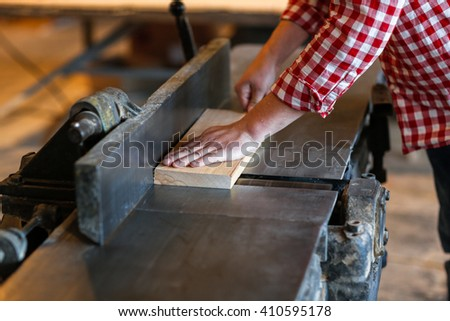 Carpenter working with  big electric planer on wooden plank works at the planer, joiner's shop, workshop