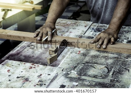 Carpenter working with Industrial tool in wood factory in grunge color