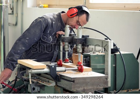 Carpenter working with wood in workshop - stock photo