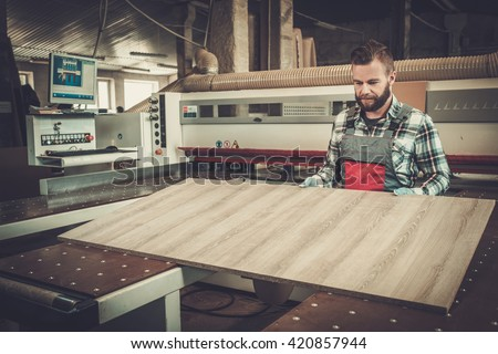 Carpenter works on wood plank in carpentry workshop. - stock photo