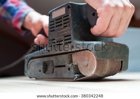 Carpenter works with belt sander in carpentry - stock photo