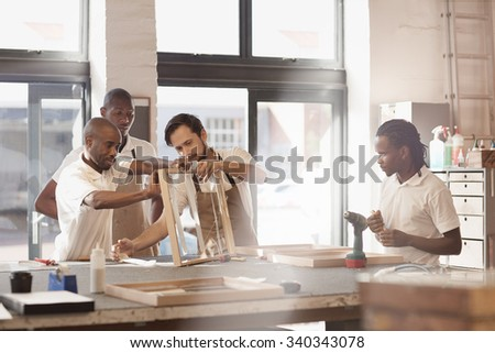 Carpenters working together on a wooden frame - stock photo