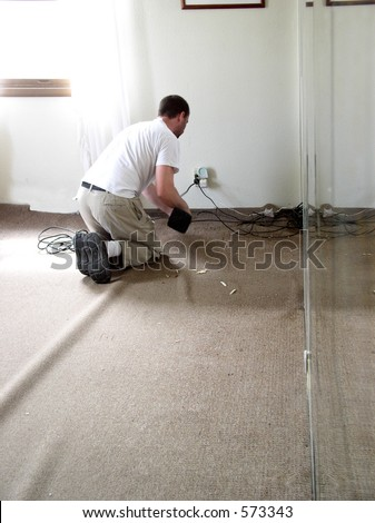 Carpet layer stretches creases out of carpet being laid - stock photo