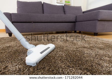 Carpet with vacuum cleaner in living room  - stock photo