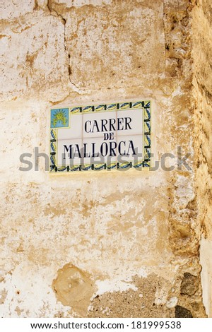 Carrer de Mallorca - old, earthenwear glazed tiles with street name on a Spanish stone wall in Palma de Majorca (Palma de Malloca), Baleares Islands, Spain - stock photo