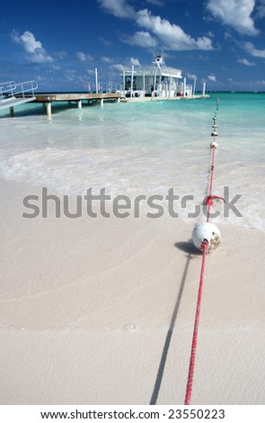 Carribean Landscape - Bouys, Pier and Ferry Boat in a Tropical Ocean, White Sand Beach - stock photo