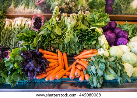 Carrot and greens in greengrocery at supermarket