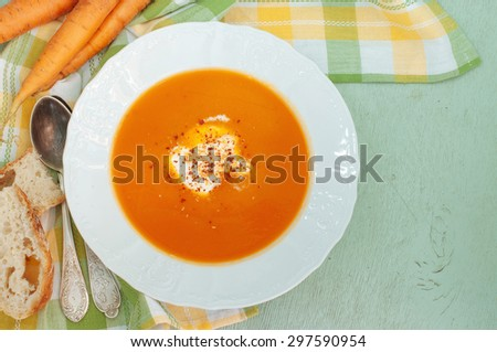 Carrot-Apple Soup on a light green wood background - stock photo