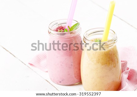 Carrot banana and raspberry shake on wooden table. Smoothie concept