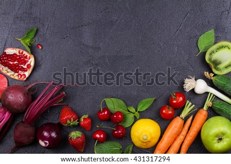 Carrot, beetroot, cucumber, lemon, pomegranate, kiwi, apples, tomatoes, cherries, strawberry, red onion, basil and mint. View from above, top studio shot of vegetables and fruits