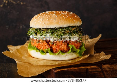 Carrot burger with clover sprouts on dark background