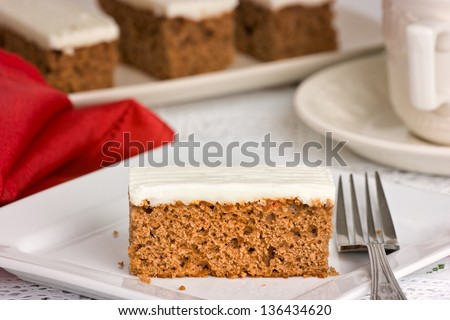Carrot Cake on a white plate with fork, tea cup & saucer. Shallow depth of field - stock photo