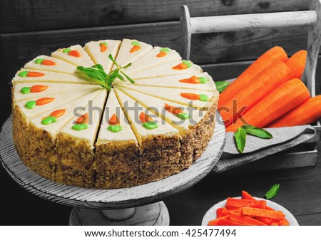 Carrot cake pie, sprinkled with nuts, decorated with cream-colored carrots on a stand for cakes, fresh carrots in a white box on a dark black background wooden table in rustic style - stock photo