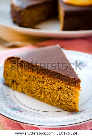 Carrot cake with chocolate topping and caramelized oranges - stock photo