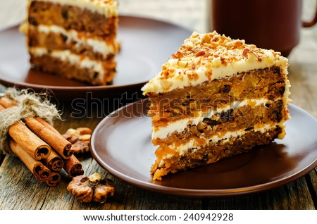 carrot cake with walnuts, prunes and dried apricots on a dark wood background. tinting. selective focus - stock photo