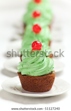 Carrot cupcakes with green whipped cream frosting and a candied cherry on top. - stock photo