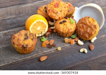 Carrot cupcakes with lemon and apple, nuts and candied fruits on wooden background - stock photo