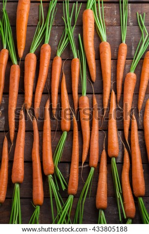 Carrot group lined on old rustic wooden table - stock photo