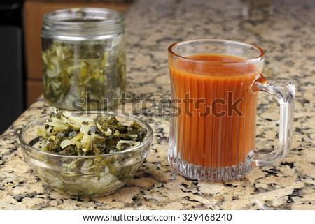 Carrot juice beverage along and a clear side dish of sauerkraut kim chi with mixed vegetables on a granite kitchen counter top. Vegetarian side dish that is healthy, has a lot of healthy fiber.