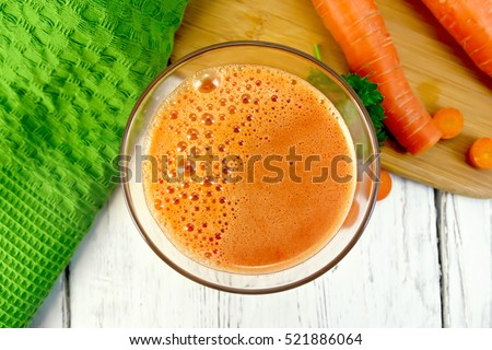 Carrot juice in a tall glass, vegetables with parsley, napkin against the background of the wooden planks on top