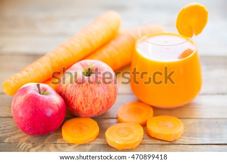 Carrot juice in glass on wooden table