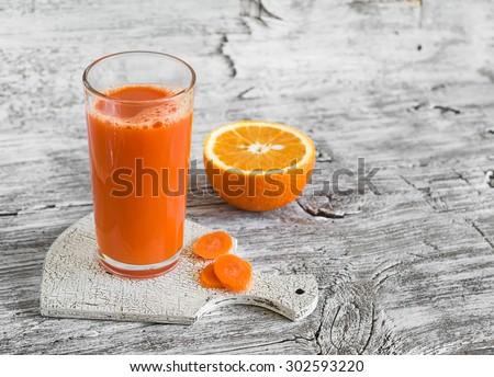 carrot-orange juice in a glass beaker on a light wooden background - stock photo